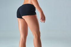 Closeup woman beautiful buttocks over grey background Royalty Free Stock Images