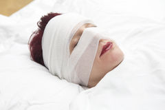 Closeup of woman in bed with bandages wrapped around her head Stock Photos