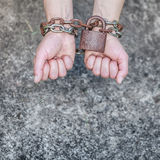 Closeup woman with chained hands and padlock. Crime, arrest jail concept. Closeup woman with chained hands and padlock on grunge background Royalty Free Stock Photo