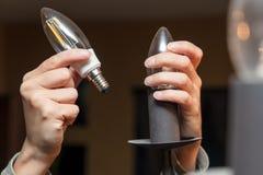 Closeup, woman changing a light bulb, energy saving lamp. Electrictiy royalty free stock photography
