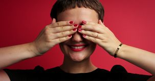Closeup of woman closed her eyes with hand and waiting a gift. surprised than. And smiling stock footage