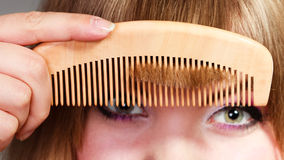 Closeup woman combing her fringe with comb Royalty Free Stock Images