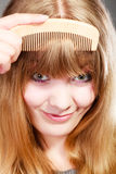 Closeup woman combing her fringe with comb Stock Image