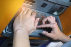 Closeup woman covering ATM machine keypad with her hands and pressing number key at the ATM machine, Hand press money from ATM. stock photo