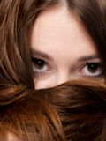 Closeup woman covers the face by long brown hairs Stock Images