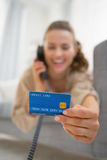 Closeup on woman with credit card talking phone Stock Photography