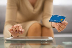 Closeup on woman with credit card using tablet pc. In living room Stock Image