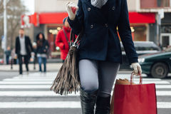 Closeup of woman crossing the street after shopping Stock Photo