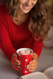Closeup on woman with cup of chocolate and book Royalty Free Stock Photos