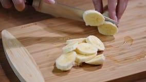 Closeup on woman cutting banana on cutting board. HD stock footage