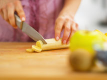 Closeup on woman cutting banana on cutting board Stock Photo