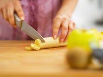 Closeup on woman cutting banana on cutting board Stock Photo