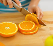 Closeup on woman cutting orange Royalty Free Stock Images