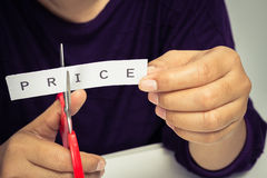 Cut price. Closeup woman cutting paper of price word Stock Photo