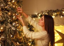 Closeup woman decorating Christmas tree New Year`s toys at home Royalty Free Stock Photos