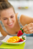 Closeup on woman decorating plate with fruits Stock Photos