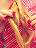 Closeup of woman doing braid on blonde hair Stock Images
