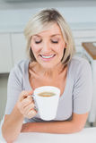 Closeup of a woman drinking coffee in kitchen Royalty Free Stock Photos