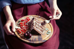 Closeup of woman eating piece of chocolate cake; selective focus. Closeup of woman eating piece of chocolate and fruit cake; wooden plate on her lap Royalty Free Stock Image