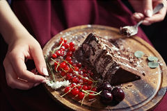 Closeup of woman eating piece of chocolate cake; selective focus. Closeup of woman eating piece of chocolate and fruit cake; wooden plate on her lap Stock Photography