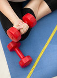 Closeup of woman exercising on fitness mat and lifting red dumbb Stock Photo