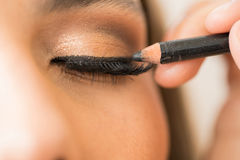 Closeup of a woman with eyeliner. Macro view of a woman`s closed eyes with fake eyelashes getting some eyeliner in a beauty salon royalty free stock images