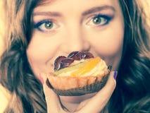 Closeup woman face and fruit cake Stock Image