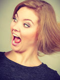Closeup woman face making crazy funny expression. Emotions expressions concept. Closeup of blonde woman face making crazy funny expression royalty free stock photo