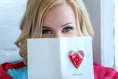 Closeup of woman face partly covered with love postcard. Royalty Free Stock Photo