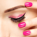 Closeup woman face with pink nails near eyes. Royalty Free Stock Photography