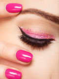 Closeup woman face with pink nails near eyes. Royalty Free Stock Images