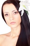 Closeup woman face portrait with lily in her hair Royalty Free Stock Photos