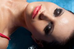 Closeup woman face with smoky eyes laying in water Royalty Free Stock Photography