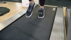 Closeup of woman feet in sneakers running on the treadmill at the gym stock footage