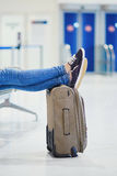 Closeup of woman feet on a suitcase in international airport Stock Photo