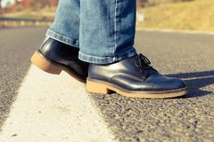 Closeup of woman feet wearing genuine leather autumn shoes. Standing in the middle of the road Stock Photos