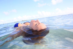 Closeup of a woman floating in crystal clear water. Closeup of woman floating in lagoon water Stock Image