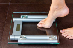 Closeup of woman foot uploading to bathroom scale Royalty Free Stock Photo