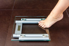 Closeup of woman foot uploading to bathroom scale. Health and weight concept royalty free stock image