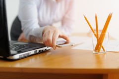 Closeup of a woman freelancer works in the office at the table. Stock Images