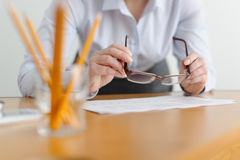 Closeup of a woman freelancer works in the office at the table. Royalty Free Stock Image