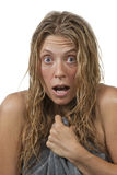 Closeup of woman gets out of the shower, surprised. Blond woman with curly hair is surprised and scared while getting out of the shower, grabs her towel. Maybe Royalty Free Stock Images