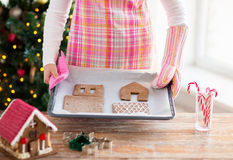Closeup of woman with gingerbread house on pan Stock Images