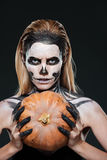 Closeup of woman with gothic skeleton makeup holding pumpkin. Over black background stock image