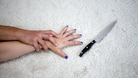 Closeup of woman grabbing a knife while being attacked by man Stock Photo