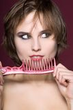 Closeup woman with hairbrush. On red background Stock Images