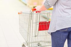 Closeup of woman hand and back with shopping cart in supermarket. Shopping concept. Selective focus with focus on hand royalty free stock image