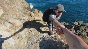Closeup of woman hand helping male friend climb the mountain top.