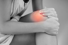 Closeup woman hand holding knee with pain on bed, health care an. Woman with knee pain close up. Pain relief concept royalty free stock images