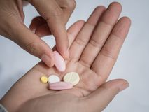 Closeup woman hand holding a pill. Healthcare, medical supplements concept Stock Photos